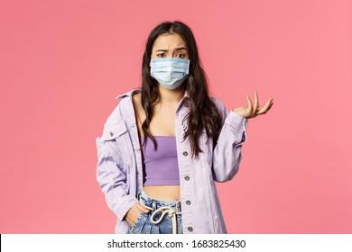 Covid19, Quarantäne, Menschen Konzept. Verwirrtes junges Mädchen schrumpelt, schau unbegreiflich aus, warum Menschen, die während des Ausbruchs einer Koronavirus-Pandemie nach draußen gehen, eine medizinische Gesichtsmaske tragen, rosafarbener Hintergrund