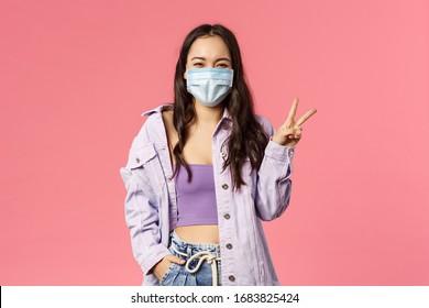 Covid19, Quarantäne, Menschen Konzept. Optimistisches, lächelndes glückliches Mädchen in medizinischer Gesichtsmaske, zu Hause, Zeichen des Friedens zeigen, während Ausbruch der Koronavirus-Pandemie, rosafarbener Hintergrund für Sicherheit sorgen