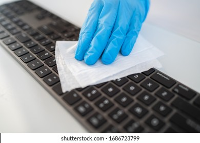 Covid-19 sanitizing office space wiping corona virus cleaning and disinfection of your workspace. Disinfecting wipes to wipe surface of desk, keyboard, mouse at office. Stop the spread of coronavirus.