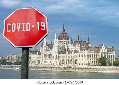 Covid-19 sign with parliament building in Budapest, Hungary. Coronavirus pandemic outbreak concept.