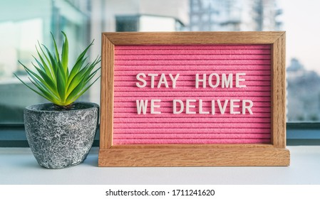 """COVID-19 """"STAY HOME WE DELIVER"""" Coronavirus social distancing restaurant business message sign with text offering online delivery to home, staying inside. Pink felt board with plant."""