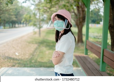 Covid-19 virus , Coronavirus protection concept. Close up Asian woman wearing protective mask and pink face shield hat for safety prevent virus. Standing alone waiting public bus or taxi transport .