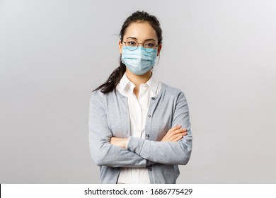 Covid19, virus, health and medicine concept. Portrait of young professional asian employee work on remote, staying safe, wear medical mask, cross hands over chest confident serious looking
