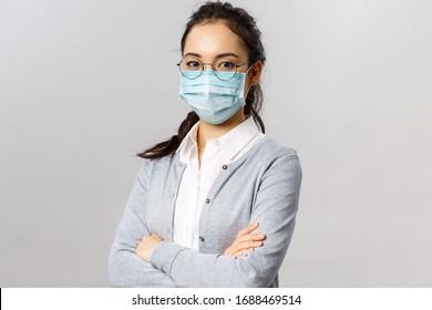 Covid19, Virus, Gesundheit und Medizin Konzept. Porträt einer jungen selbstbewussten asiatischen Krankenschwester, die sich um die Patienten kümmert, während des Quarantäncoronavirus eine ärztliche Maske trägt, Brust überqueren