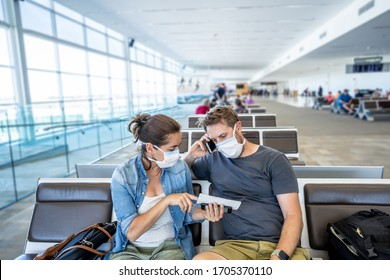 COVID-19 worldwide borders closures. Couple with face mask stuck in airport terminal after being denied entry to other countries. Passengers stranded in airport on his travel back to home country.