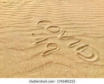 Covid-19 écrit dans le sable sur une plage tropicale pendant une journée chaude