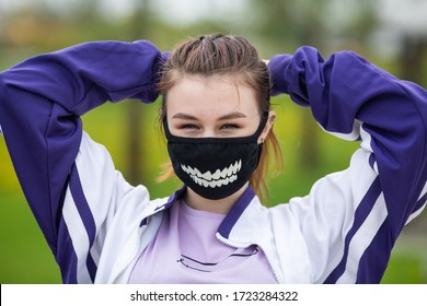 COVID-19. Young caucasian teen girl in a black mask goes in for sports on a street sports ground during a pandemic. Coronavirus in Europe.