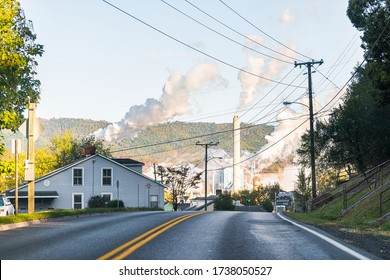 Covington, USA - October 18, 2019: Virginia city in Alleghany county with street road in small town and pollution from WestRock paper mill smokestacks