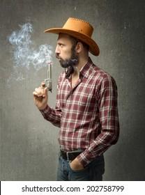 cow boy blowing on smoke gun