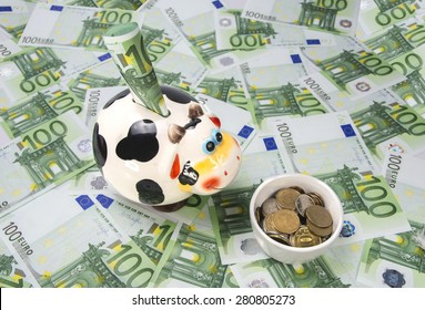 cow a moneybox on a green field of euro notes and a feeding trough of coins