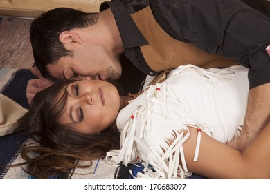 A cowboy is about to kiss an Indian's neck while they lay on a blanket.