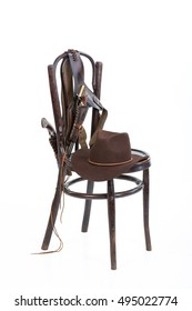 Cowboy belt, guns and hat on an old chair on isolated background