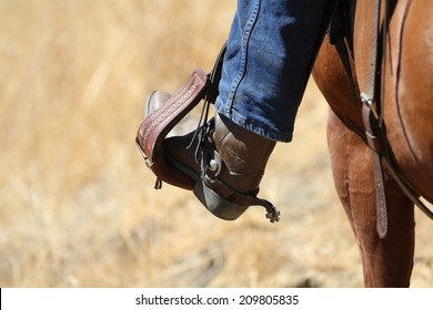 A cowboy boot in saddle stirrup.