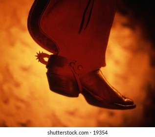 Cowboy boot with spur flying as if being bucked off a bronco.
