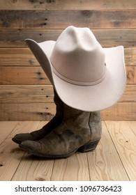 Cowboy boot and western hat on wooden background.