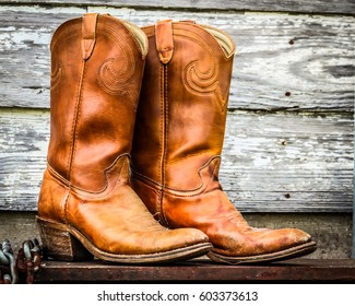 Cowboy boots and chains on weathered wood
