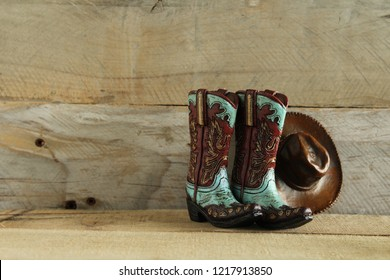 cowboy boots and hat on a natural wood background with writing space