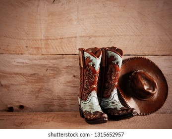 cowboy boots and hat with sepia wood background with writing space