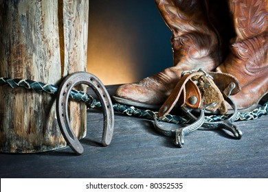 ,Cowboy boots,horseshoe,whip and spurs on wood,