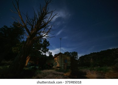 Cowboy bunkhouse and night sky with large juniper tree in foreground.    The blue night sky has a few clouds and stars while a sandstone canyon rim is in the background.