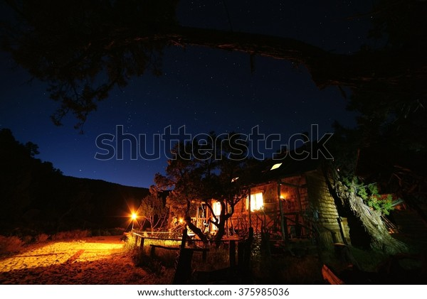 Cowboy cabin and the night sky with a juniper branch in the foreground.  This Utah cabin is located in the desert at the base of the high Uinta mountains of Utah.  It is off the grid.