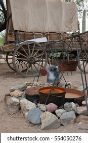 Cowboy campfire in front of a covered wagon during daytime