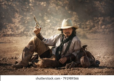 Cowboy carrying a gun, sitting outdoors.