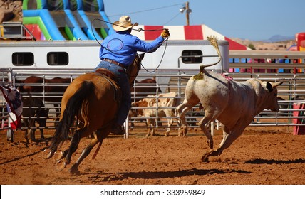 A cowboy chasing a bull with a rope on a rodeo event, Utah, USA