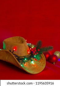 Cowboy Christmas.American West cowboy hat on christmas red background for text