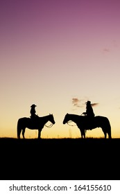 Cowboy and cowgirl silhouette at colorful sunset