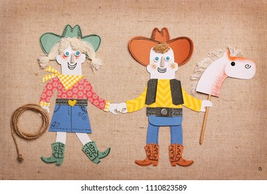 Cowboy and cowgirl in western clothes with lasso and skick horse toy.Paper application