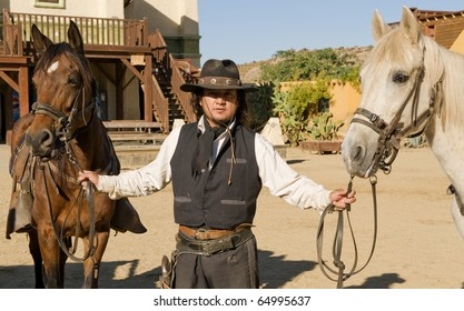 Cowboy Deputy Sheriff hilding two horses by the reins