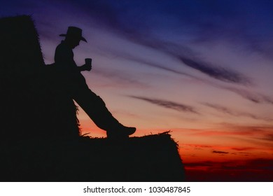 A cowboy drinking a beer at the end of a long day.