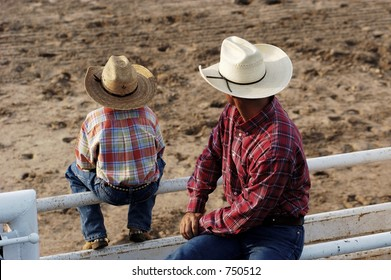 Cowboy father and son watching rodeo action.