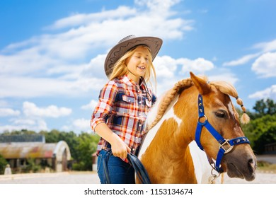 Cowboy girl. Cute smiling cowboy girl feeling extremely happy while leading little beautiful pony