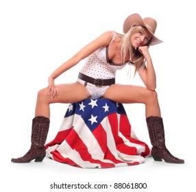 Cowboy girl sitting on a american flag.