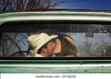 Cowboy and girlfriend kissing in through the back window of a pickup truck