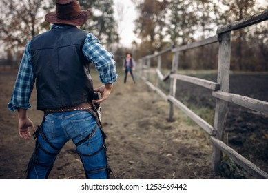 Cowboy with gun prepares to gunfight, back view