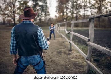 Cowboy with gun prepares to gunfight, back view