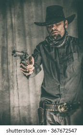Cowboy Gunslinger Pointing Gun. Cowboy gunslinger aiming a classic colt 45 pistol off camera. Edited with a vintage film effect. (Focal point is the gun, NOT the cowboy)
