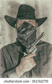 Cowboy Gunslinger Poses for Portrait. Gun-slinging cowboy bandit poses for a portrait. Edited with a vintage film effect.
