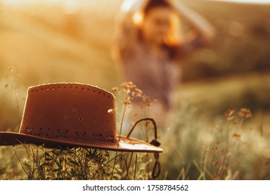 cowboy hat and girl in the background concept work in the field or on the ranch