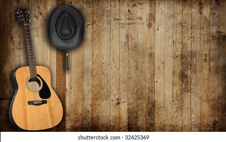 Cowboy hat and guitar against an old barn background.