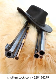 Cowboy hat and guns on a sheep fur.