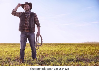 Cowboy in a hat and with a lasso standing in a field at sunset