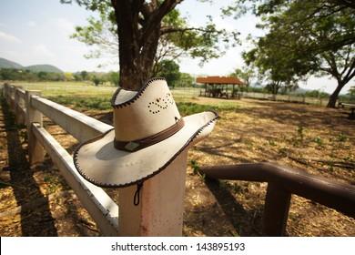 cowboy hat, light brown cowboy hat hanging on farm fence