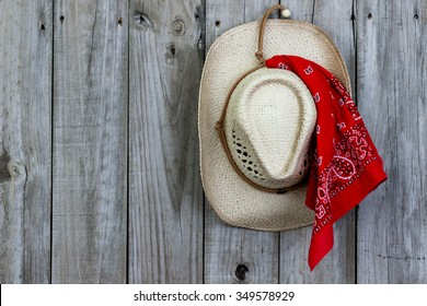 Cowboy hat with red bandanna hanging on antique rustic wooden background