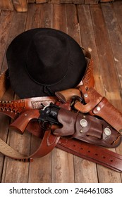 Cowboy hat, revolvers, and holsters on a wooden background.