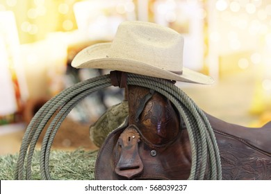 A cowboy hat and rope on a saddle.