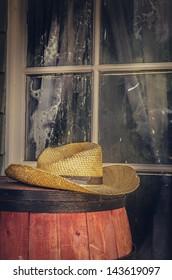 Cowboy hat sitting on barrel outside western style window